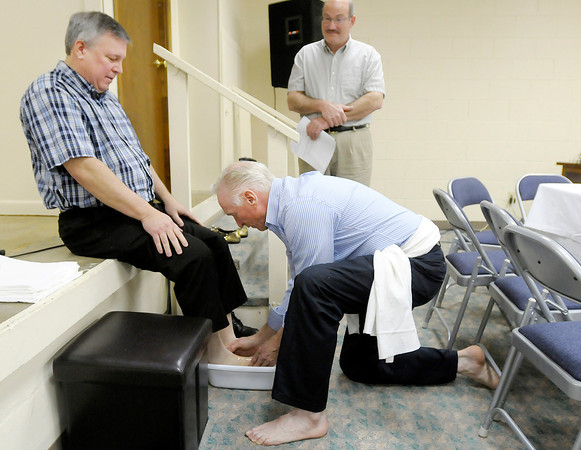 Dave Score washes Brian Poore's feet as Christ Lutheran Church held a Christian Passover Seder on Maundy Thursday. The church took part in a Seder meal adapted from the traditional Jewish celebration of Passover.