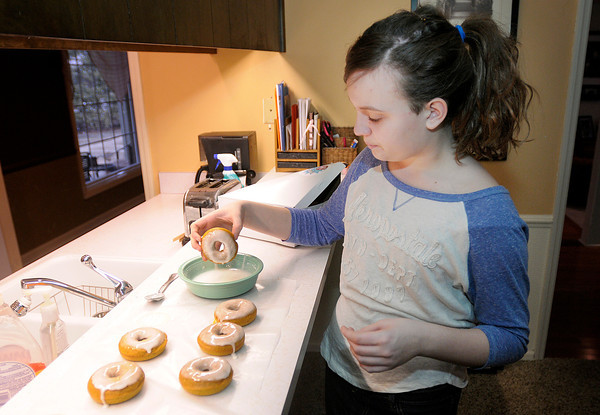 Proprietor of Emma D's Bakery, twelve-year-old Emma Williams, prepares a batch of doughnuts. Instead of receiving an allowance Williams earns her own money baking and selling doughnuts on the weekend.