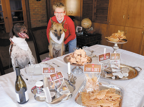 Cindy Dunston Quirk poses for a photo with her dogs Scout and Zoe and her company's new products Chicken Jerky and Sweet Potato Treats. The long search for chews that wouldn't upset her dogs allergies led to the development of the products sold by Scout and Zoe's.