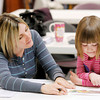 Edgewood Elementary kindergarten teacher Autumn Pratt gives Aubrey Smith, 4, a basic skills assessment during Anderson Community School's kindergarten registration at Mounds Mall on Friday.