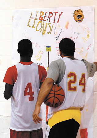Liberty Christian players read the notes of encouragement on the large poster that is on the wall in the gym during a break in practice Tuesday.