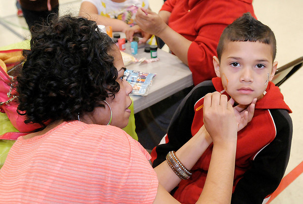 Candace Stewart paints seven-year-old Elvin Acree's face during the Easter Eggs-Extravaganza hosted by New Life Apostolic Church at the UAW on Saturday.