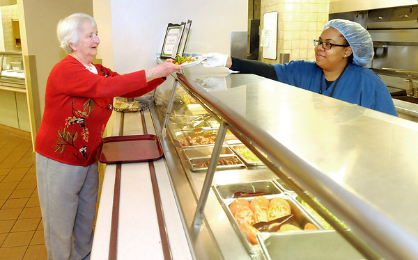 Ashley Lenoir serves a meal to Donna Jones in the cafeteria at Community Hospital. The hospital is offering two vouchers a month to seniors.