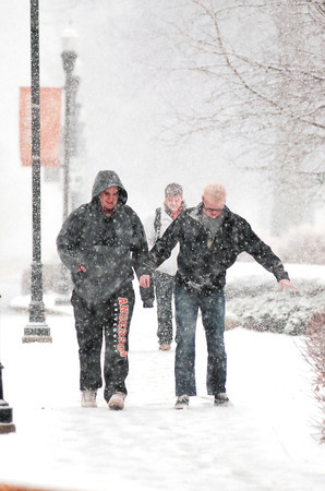 Wet snow started falling in the Anderson area late Tuesday afternoon quickly covering the streets with a coating of sloppy snow.  These AU students watch their footing as they walk through campus.