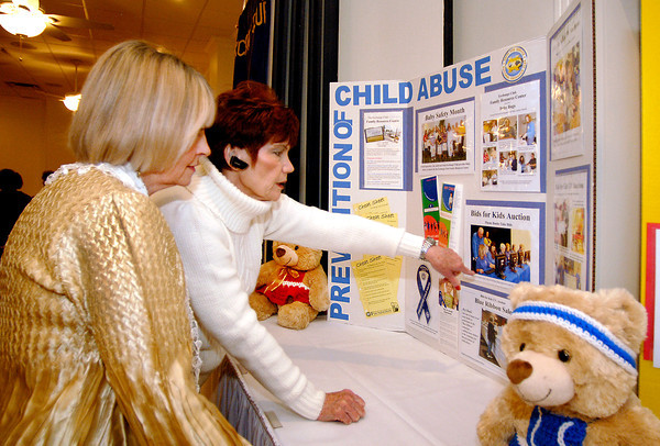 Anderson Noon Exchange Club member Ginger Shanks, right, shows her guest Judy Hatley some of the photos in a display for the 25th anniversary of the Bids for Kids auction for the prevention of child abuse at their luncheon Tuesday.