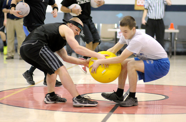 Anderson High School's Jason Cramer, left, and APA's Trent Scifres grab for the same ball during the start of a game of dodgeball at the Geater Center on Friday. The Madison County chapter of Students Against Destructive Decisions (SADD) organized the dodge ball tournament. All the Madison County high schools participated by sending at least one team.