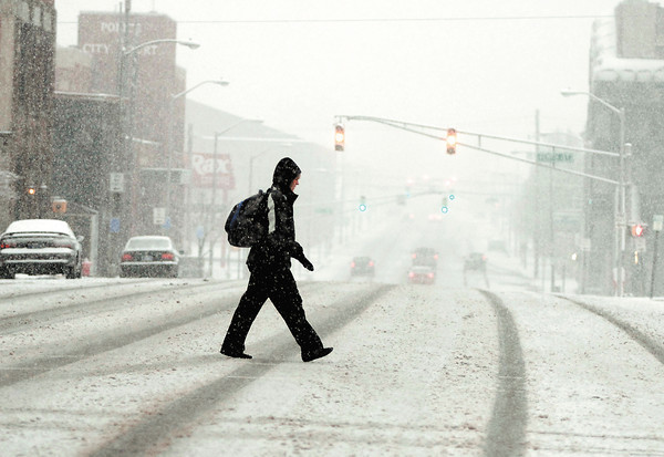 Wet snow started falling in the Anderson area late Tuesday afternoon quickly covering the streets with a coating of sloppy snow.  This person crosses Main Street in downtown Anderson.