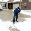 Jon Bell shovels his driveway on Schell Lane in the Paramount Springs neighborhood on Wednesday.