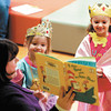 Eliza VanAlst, 4, and sister Cadence, 5, are enthralled by Heather Sullivan's reading of I Can Read with My Eyes Shut by Dr. Seuss during Preschool Promenade at the Anderson Public Library.