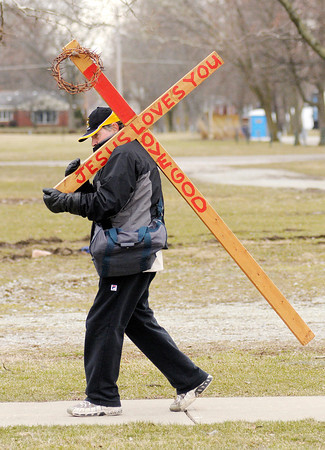 Carl Bowen carries a cross down University Boulevard on Thursday afternoon. He has been using the cross as a way to spread the gospel since 2009. A member of the Linberg Road Church of Christ, this week he is carrying it as part of 7 days of fasting and prayer being undertaken by the church as they face an uncertain future due to a life insurance financing plan that failed leaving the church facing foreclosure.