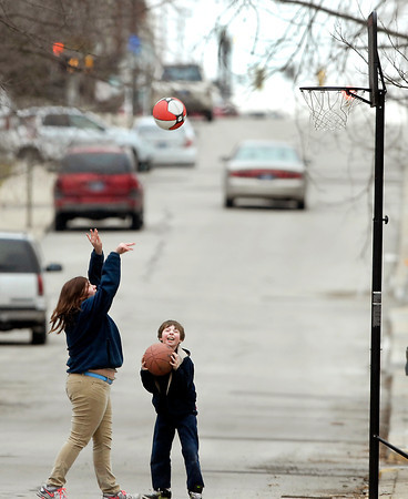 Neighbors Bailey Walker, 15, and Kyan Lehr, 8, shoot hoops in front of their homes along west 10th Street Monday afternoon.  They took advantage of the dry weather to get outside and play since a weather system will bring rain, ice, and snow to the area the next several days.