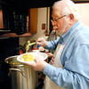 THB photo/John P. Cleary<br /> Trinity Episcopal Church volunteer Larry Coates fills a plate with Chicken and noodles as he and others dish up lunch during the church's Midweek Meal.