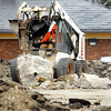 John P. Cleary | The Herald Bulletin<br /> A Anderson Street Department worker uses a jack-hammer attachment to bust up a large section of concrete as crews work to remove the asphalt parking surface of the old Edgewood Plaza to make the space into a temporary park.