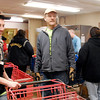 John P. Cleary / The Herald Bulletin<br /> Phil Sveum, volunteer pantry manager for St. John's Evangelical Lutheran Church's Helping Hands Food Pantry, stands between the two food lines to help keep things moving.
