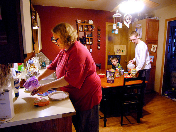John P. Cleary / The Herald Bulletin<br /> Rachel Brown gets out veggies as Jonathan, 15, pours drinks as Jacob, 3, waits for dinner time.