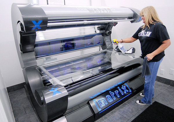 Don Knight / The Herald Bulletin<br /> Pam Blueher cleans a Matrix tanning bed at A Total Tan in Anderson on Friday. The legislature passed a law making it illegal for children 16 or younger to use tanning beds.