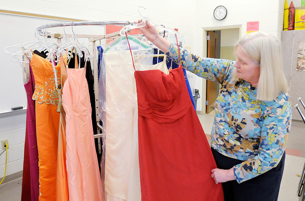 Don Knight / The Herald Bulletin<br /> Anderson High School prom sponsor Vickie Elrod looks at dresses that have been donated to the school for girls needing a dress for the prom. She originally sold gowns for cheap as a fundraiser, but after a surge in donations, she started giving them away for free last year.