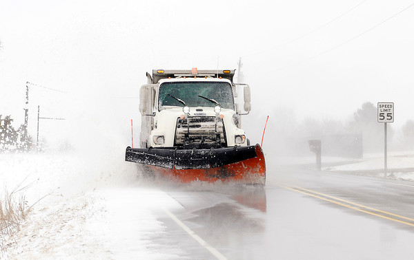 Don Knight / The Herald Bulletin<br /> A Madison County plow truck clears snow that was blowing onto County Road 800 North on Wednesday.