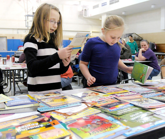 Don Knight / The Herald Bulletin<br /> From left, Haylee Malston and Larissa Rominger pick out books after scoring a Bingo during Book Bingo at Alexandria-Monroe Elementary School on Thursday.