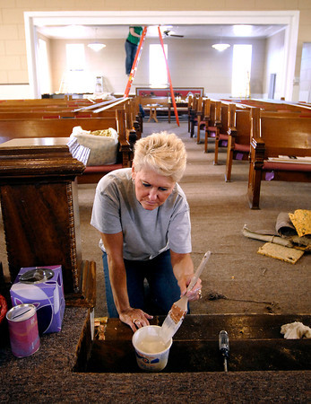 John P. Cleary / The Herald Bulletin<br /> Volunteers are restoring Summitville United Methodist Church's sanctuary. Here Reta Holdcraft does some painting along the front of the church.