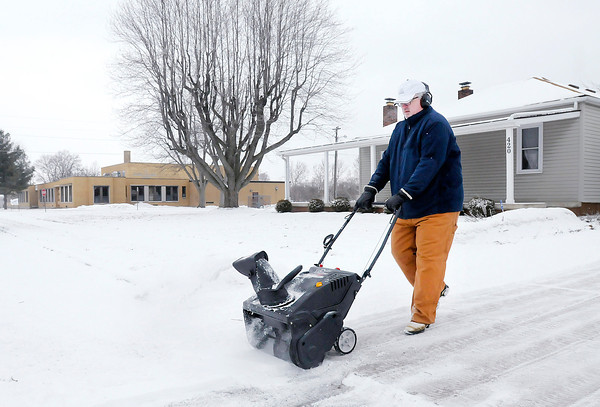 Don Knight / The Herald Bulletin<br /> Tim Ogburn uses a snow blower to clear his driveway on 37th Street on Saturday afternoon. A second wave of snow was forecast to possibly bring additional accumulation.
