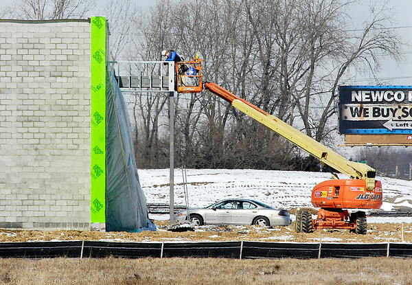 THB photo/John P. Cleary<br /> This worker, using a lift, does some metal work Tuesday over the entrance of one of the new Myer Autoworld dealership buildings being constructed along south Scatterfield Road in Anderson.  Work has progressed on the new development despite the harsh winter weather.