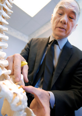 John P. Cleary / The Herald Bulletin<br /> Dr. Charles Howe points out a area of lower spine that can cause pain.