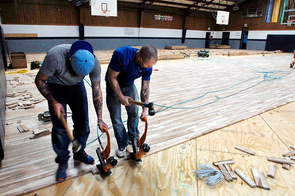 John P. Cleary / The Herald Bulletin<br /> Nicholas  Bankowski and Kasey Corbit, of Kiefer Specialty Flooring, nail together pieces of the new hard wood gym floor at the Geater Center they are installing.