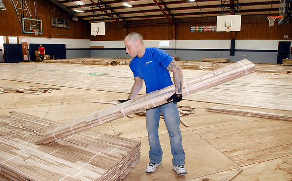 John P. Cleary / The Herald Bulletin<br /> Kasey Corbit, of Kiefer Specialty Flooring, gets another bundle of 2 1/4 inch wide hard maple pieces for the new gym floor being installed at the Geater Center by the Linhurst, Ill. company.
