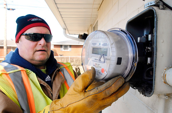 THB photo/John P. Cleary<br /> Steve Price, of the connect/disconnect service of the City Meter Department, installs a new electric meter at this address in east Anderson Friday afternoon.