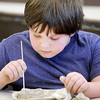 Don Knight | The Herald Bulletin<br /> Kieran Caudill, 8, decorates a bowl he created during a Prehistoric Pottery activity at the Mounds State Park Nature Center on Friday. The event was the last of a week of activities planned for students on Spring Break.