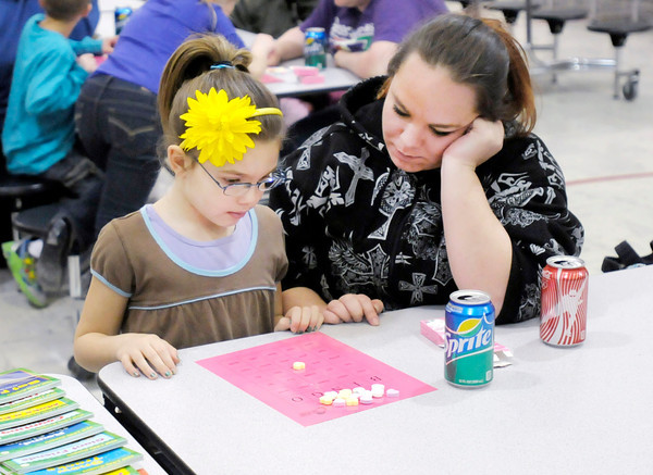 Don Knight / The Herald Bulletin<br /> Mya Murphy, 7, plays Book Bingo as her mother Jessica looks on at Alexandria-Monroe Elementary School on Thursday. Students searched for sight words on their bingo cards as they were called out.