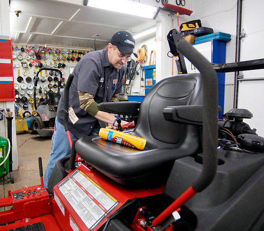 THB photo/John P. Cleary<br /> Max Taylor cleans up this mower as he prepares it for pickup by the owner at Bindle Lawn Equipment Sales & Service.  With the severe winter weather repair shops have had a backup in tractor repairs since people haven't been able to get their tractors out of their barns and to the repair shop.