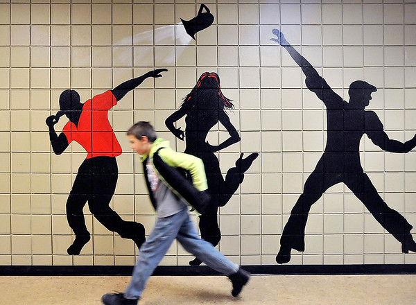 John P. Cleary |  The Herald Bulletin<br /> Sixth grade Highland Middle School student Caulin Huffman hustles his way past the large silhouettes painted along the hallway of the music department as he heads for class Thursday afternoon. The department has painted their halls with multiple figures of musicians, dancers and performers.