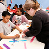 Don Knight | The Herald Bulletin<br /> Sheila Walling helps John Hopkins, 12, make a wallet with tape during Spring Break Camp at the Boys and Girls Club on Tuesday.