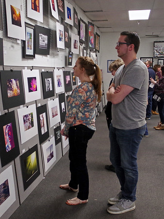 Katelyn Haywood and Cody Pratt enjoy the art works of local students during the Art Association of Madison County's exhibition on Sunday.