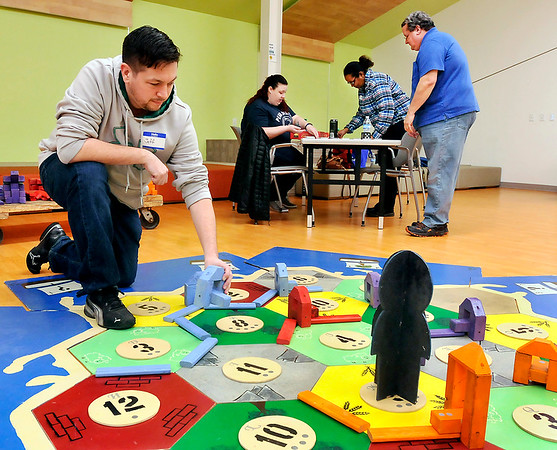 John P. Cleary |  The Herald Bulletin<br /> Jeff Keith, of Lapel, places his settlement piece on the giant floor version of the game CATAN while the other players, Whitney Morgan, Senetra Herndon, and Darrell King, all from Anderson, prepare for their turns during Game Night for Grownups at the Anderson Public Library Monday. The library holds a monthly gaming group for adults only and features a game of the month to learn how to play.