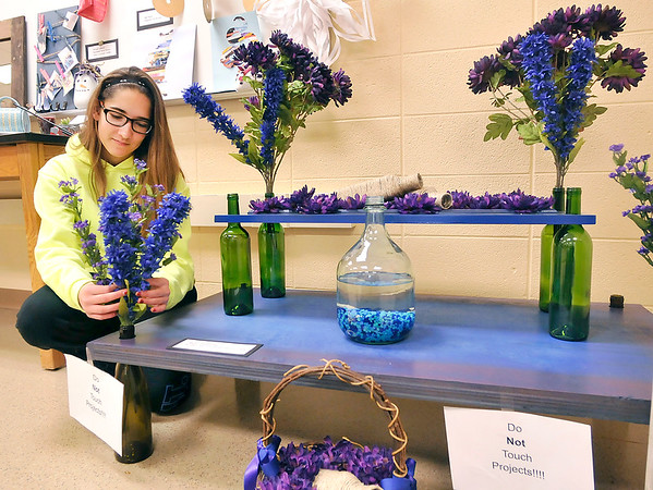 John P. Cleary |  The Herald Bulletin<br /> Recycle & Reuse projects from Cyndee McFarran's 8th-grade Alexandria-Monroe Jr. High School science class. Alliyah Standridge made this reclaimed wood table with bottle legs from items from her sisters wedding.
