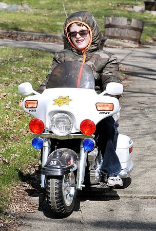 John P. Cleary |  The Herald Bulletin<br /> EJ Stafford, 8, enjoys the start of his spring break by getting on his battery-powered police motorcycle and riding the sidewalks of his neighborhood along Haverhill Drive Thursday afternoon. Stafford is a second-grader at Anderson Preparatory Academy which started their spring break for students Thursday with a early dismissal.