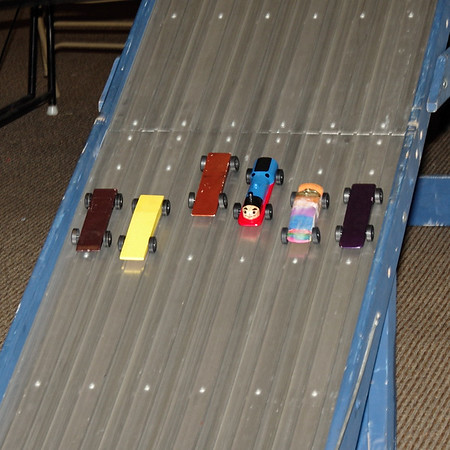 Powered solely by gravity, the Pinewood Derby cars made by Sakima District Cub Scouts streak down a specially designed aluminum track.