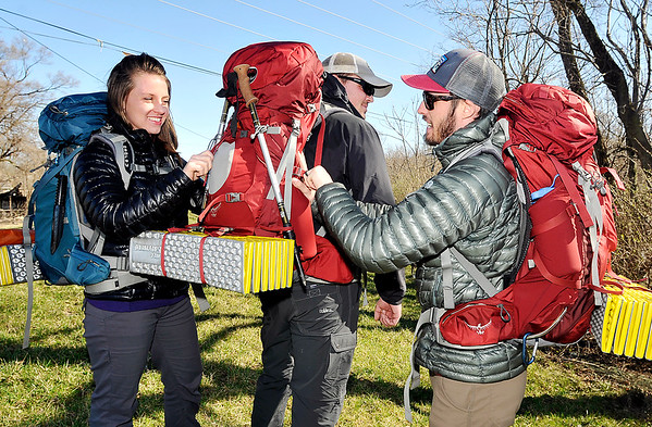 John P. Cleary |  The Herald Bulletin<br /> Jordan Carter, left, and Kyle Carter, right, Check Brock Fesmire's backpack as the trio prepare to leave to walk the Appalachian Trail for six months.