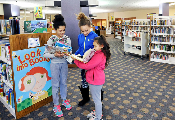 John P. Cleary |  The Herald Bulletin<br /> Janisse Martin, 8, Janyla Davison, 10, and Abrianna Hux, 7, check each others books out as they spend time in the Anderson Public Library's children's department this past Wednesday. The library plans a $500,000 remodeling of the area later this year.