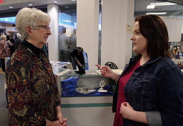 "Kasey Long describes the construction used to create her winning necklace and earrings set titled, ""Gypsy Blues,"" to Kathy Fehrman during the Art Association of Madison County's 18th Annual Student Exhibition on Sunday at the Mounds Mall."
