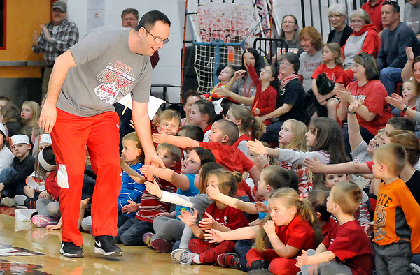 John P. Cleary |  The Herald Bulletin<br /> Frankton High School head basketball coach Brent Brobston greets the elementary students with hand slaps after being intoduced to the crowd at the state finals pep rally Friday afternoon.