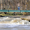 John P. Cleary |  The Herald Bulletin<br /> This man watches the rushing water hit the falls at Falls Park in Pendleton Wednesday afternoon from overhead on the foot bridge. After the heavy rains from Monday the water levels along the area waterways were still up.