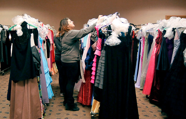 John P. Cleary |  The Herald Bulletin<br /> Carolina Garcia, 15, a Anderson High School freshman, goes through the racks of dresses Saturday during the Project Fairy Godmother Prom Dress Giveaway at Anderson Public Library.