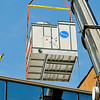John P. Cleary |  The Herald Bulletin<br /> This worker on the roof of the Madison County Government Center guides the crane operator with hand signals as they lift a cooling tower for the new cooling system for the building in place Thursday morning.