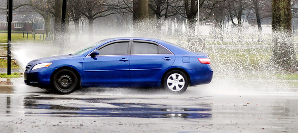 John P. Cleary |  The Herald Bulletin<br /> Approximately 1 1/2 inches of rain fell in the Anderson area Monday as rain and thunderstorms moved through the area in several waves leaving ponding water on some roadways for vehicles to navigate through like this car driving along University Blvd.