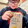 "John P. Cleary |  The Herald Bulletin<br /> Highland sixth-graders in Mary Ann Wildman's High Ability Language Arts class makes ""random acts of kindness"" bags. Here Robby James, 12, ties ribbons onto the top of his decorated bag."
