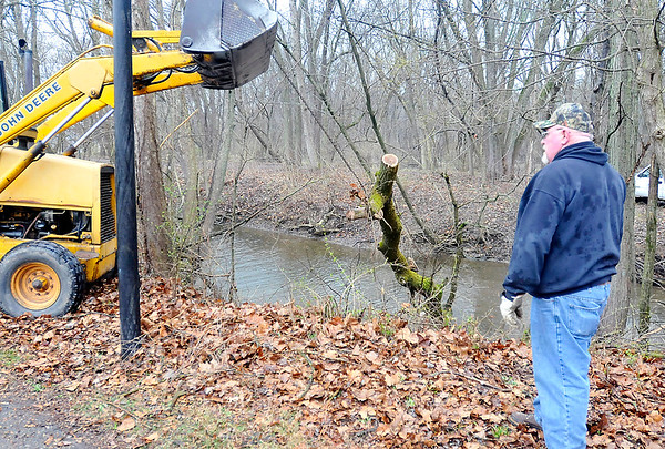 John P. Cleary |  The Herald Bulletin<br /> Workers from the Anderson Parks and Recreation Department use a payloader to pull this tree out of the channel at Shadyside Lake Monday. Workers had to get in the water to cut the base of the tree loose so they could pull it out and open up the waterway.